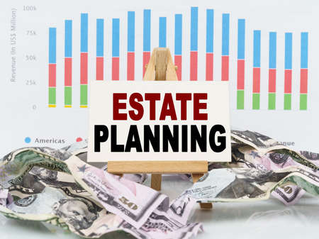Business and finance concept. Among financial charts and money is a sign with the text - ESTATE PLANNING