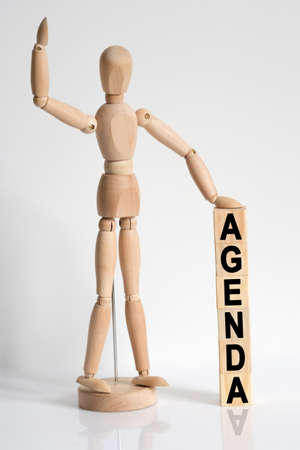 Business and medicine. The wooden man raised his hand, and under his left hand he has cubes with the inscription - AGENDA