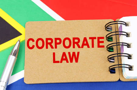Law and justice concept. Against the background of the flag of South Africa lies a notebook with the inscription - CORPORATE LAW