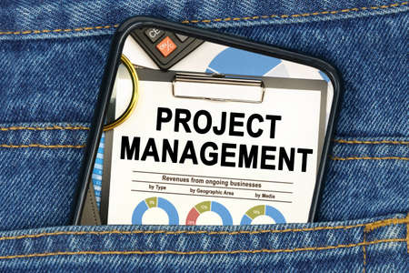 Business and finance concept. In a pocket of jeans there is a smartphone on the screen of which the text - PROJECT MANAGEMENT