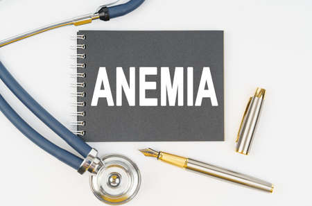 Medicine and health. On a white background lie a stethoscope, a pen and a notebook with the inscription - ANEMIA