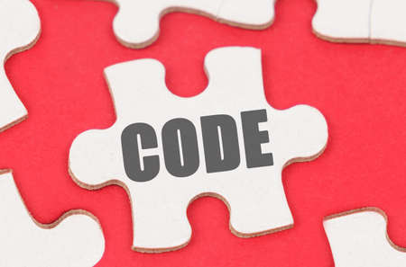 Business and Economics. On a red background, among white puzzles lies a puzzle with the inscription - CODE