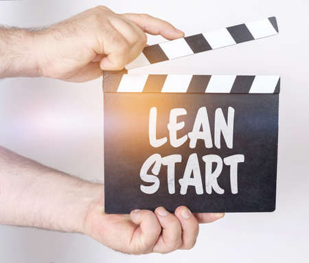 Business and finance concept. On a white background, a man holds a clapperboard in his hands on which it is written - LEAN START