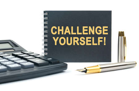 Business and finance. On a white background, there is a calculator, a pen and a black notebook with the inscription - CHALLENGE YOURSELF 免版税图像