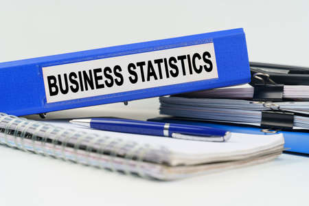 Business and finance concept. On the table are a notebook, a pen, documents and a folder with the inscription - BUSINESS STATISTICS 免版税图像