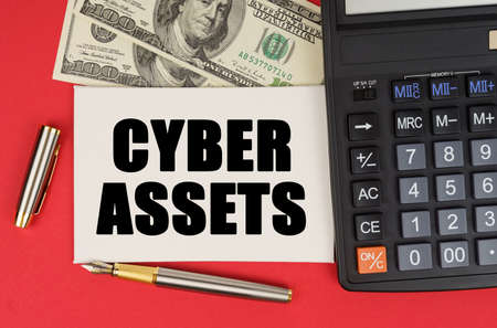 Business and finance concept. On a red background, among the money, a calculator and a pen lies a sign with the text - CYBER ASSETS 免版税图像