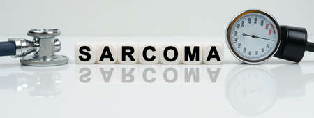 Medicine concept. On a reflective white surface lies a stethoscope and cubes with the inscription - SARCOMA