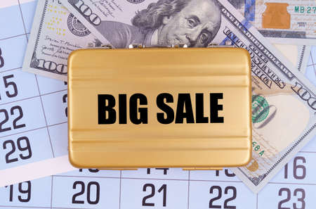 Business and finance. On the table lies a calendar, money and a briefcase with the inscription - BIG SALE