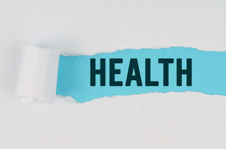 Medicine and health concept. In the middle of a white sheet of paper, a tear is made under which, on a blue background, the inscription - HEALTH