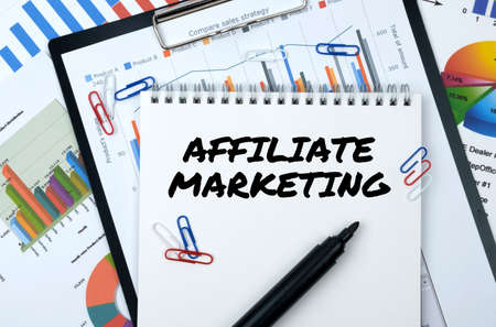 Business and finance. On the table are reports, charts, a notebook with the inscription - AFFILIATE MARKETING