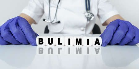 Medicine and health concept. The doctor put together a word from cubes BULIMIA 免版税图像