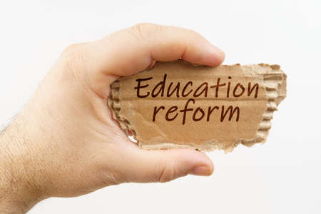 Education. A man holds a cardboard in his hand on which it is written - Education reform 免版税图像
