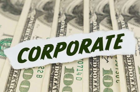 Business and finance concept. On the background of dollars lies a piece of paper with the text - CORPORATE