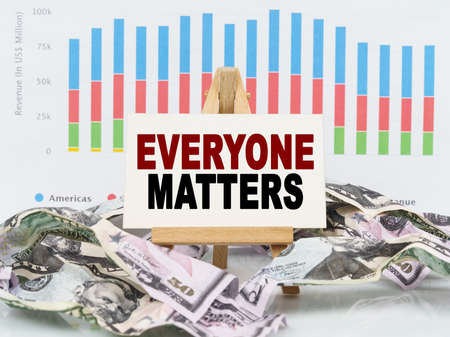 Business and finance concept. Among financial charts and money is a sign with the text - EVERYONE MATTERS