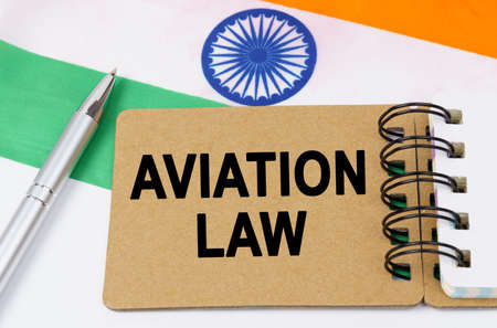Law and justice concept. Against the background of the flag of India lies a notebook with the inscription - AVIATION LAW
