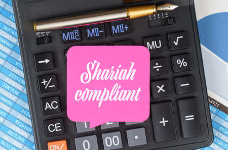 Finance and economics concept. On the desktop are charts, reports, a calculator and a sheet for notes on which it is written - Shariah compliant 免版税图像