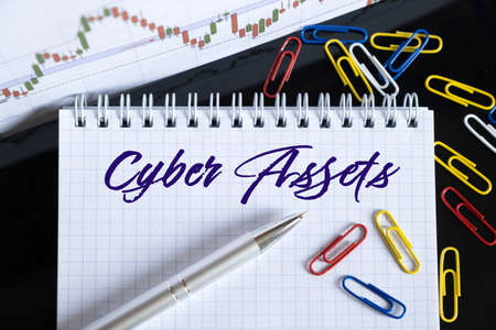 Finance and economics concept. On the desktop are a forex chart, paper clips, a pen and a notebook in which it is written - Cyber Assets