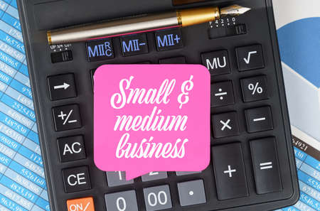 Finance and economics concept. On the desktop are charts, reports, a calculator and a sheet for notes on which it is written - Small and medium business Archivio Fotografico