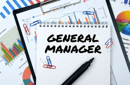 Business and finance. On the table are reports, charts, a notebook with the inscription - GENERAL MANAGER
