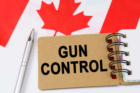 Law and justice concept. Against the background of the flag of Canada lies a notebook with the inscription - GUN CONTROL