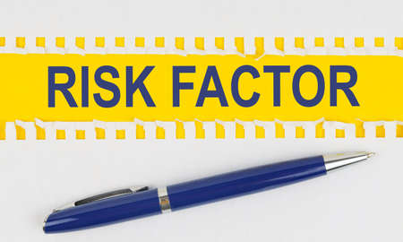 Business and finance. On the table are two sheets from a notebook and a pen on a yellow background written - RISK FACTOR