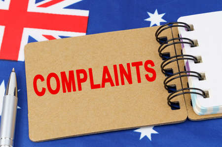 Law and justice concept. Against the background of the flag of Australia lies a notebook with the inscription - COMPLAINTS