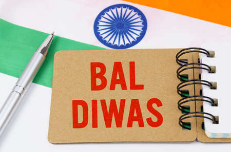 Holidays in India. Against the background of the flag of India lies cardboard with the inscription - Bal Diwas Reklamní fotografie