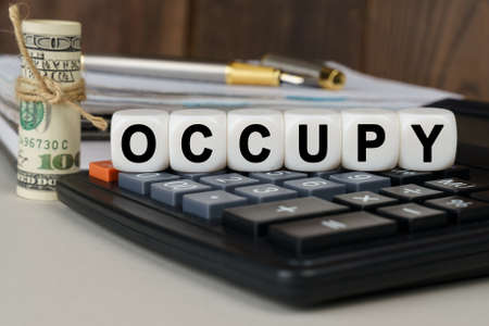 Business and finance concept. There are cubes on the calculator that say - OCCUPY. Nearby out of focus - dollars, notebook and pen