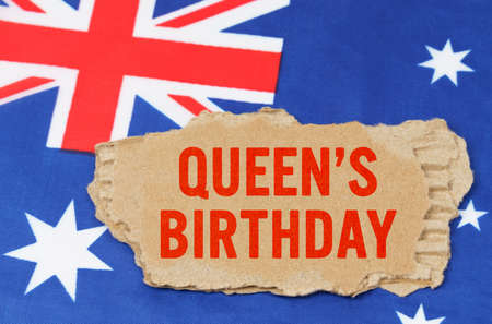 Australian National Holidays. Against the background of the flag of Australia lies cardboard with the inscription - Queens Birthday