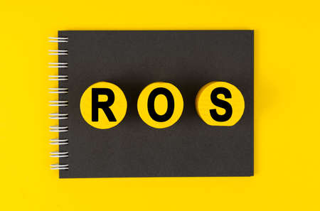 Business and finance concept. On a yellow background lies a black notebook, yellow wooden circles with the inscription - ROS