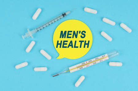 Medicine and health. On a blue background, among the pills, a thermometer and a syringe lies a sticker with the inscription - MEN S HEALTH Imagens