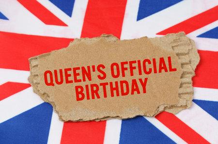 """英国的假期。在英国国旗的背景下放置着写有""""女王的官方生日""""字样的纸板"""