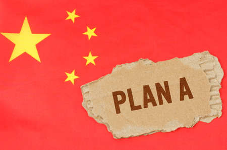 Business and finance concept. Against the background of the Chinese flag lies cardboard with the inscription - PLAN A