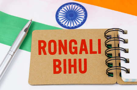 Holidays in India. Against the background of the flag of India lies cardboard with the inscription - Rongali Bihu
