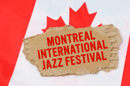 Holidays in Canada. Against the background of the flag of Canada lies cardboard with the inscription - Montreal International Jazz Festival