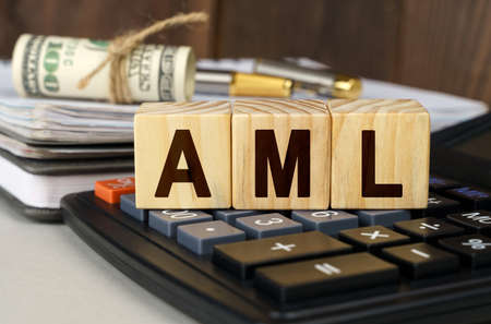Finance and economics concept. On the table are money, a calculator, a notebook and cubes with the inscription - AML Stock Photo