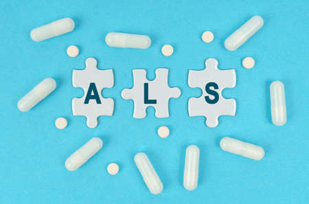 Medicine and health. On a blue background, there are pills and puzzles with the inscription - ALS Stock fotó