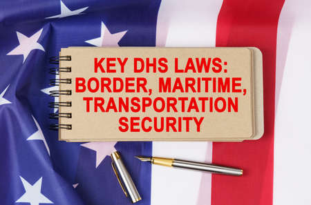 Law and order concept. Against the background of the flag of the United States of America lies a notebook with the inscription - KEY DHS LAWS
