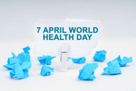 Medicine and health concept. On a white background, there are blue pieces of paper and a clothespin with paper on which it is written - 7 APRIL WORLD HEALTH DAY Imagens