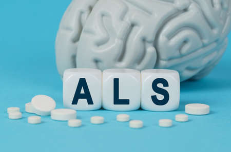 Medicine and health. Cubes lie on the table among the pills and imitation of the brain. The text on the dice - ALS