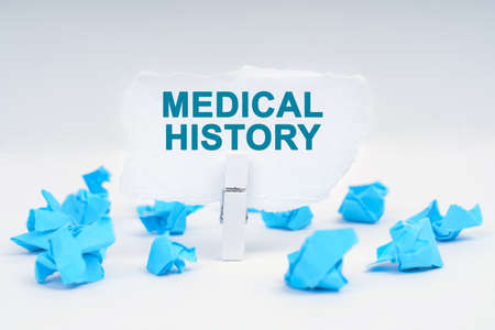 Medicine and health concept. On a white background, there are blue pieces of paper and a clothespin with paper on which it is written - MEDICAL HISTORY