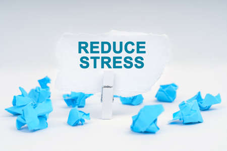 Medicine and health concept. On a white background, there are blue pieces of paper and a clothespin with paper on which it is written - REDUCE STRESS