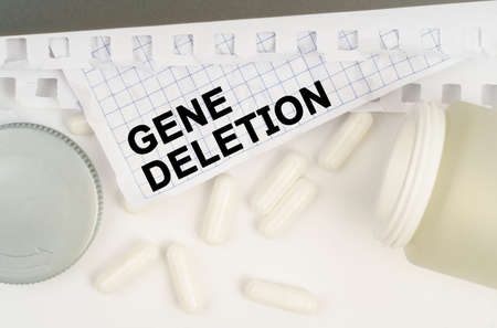 Medicine and health concept. On the table is an open jar of pills and a sheet of paper with the inscription - Gene deletion