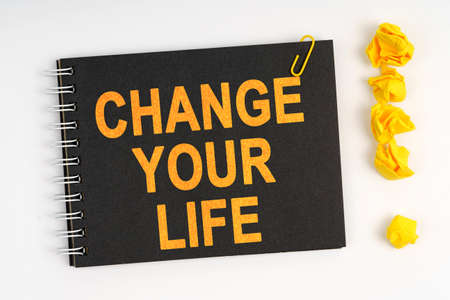 Business concept. On a white background lies a marker, an exclamation mark made of paper and a notebook with the inscription - CHANGE YOUR LIFE
