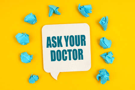 Medicine concept. On a yellow background, blue pieces of paper and a sign with the inscription - ASK YOUR DOCTOR