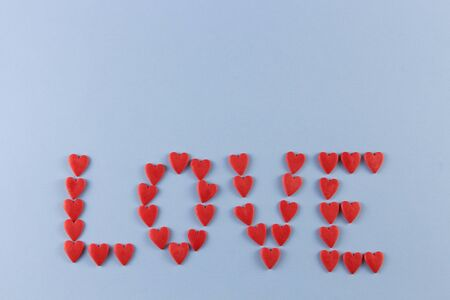 word love laid out of red hearts on a blue background