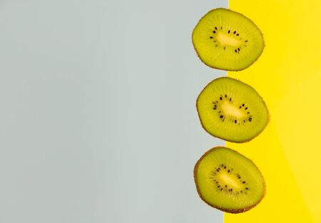 Sliced kiwi isolated on yellow-blue background. Copyspace for text