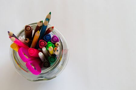 Multi-colored tags and pencils in a glass on a white background top view. School supplies.copyspace for text.