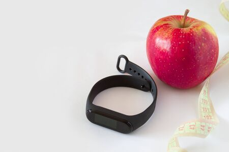 smart watch with black tape measure bracelet and red apple on a white backgroundcopyspace for text
