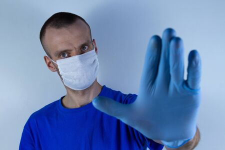 Doctor in a protective mask on a blue background. Holds an outstretched hand in front of him in a glove. Warns and stops.